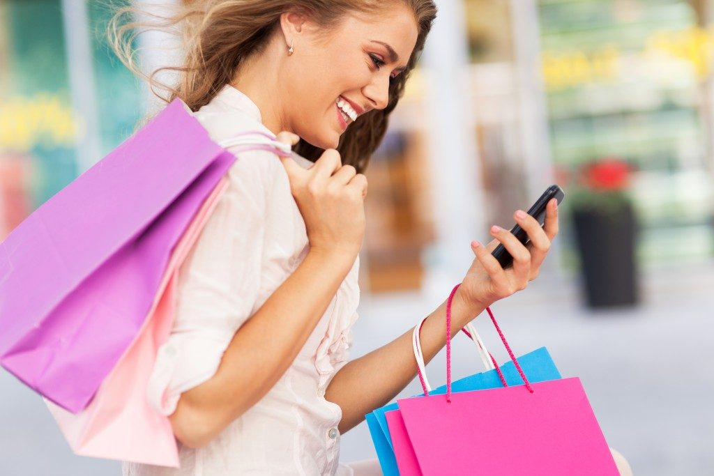 Women shopping while looking at her phone