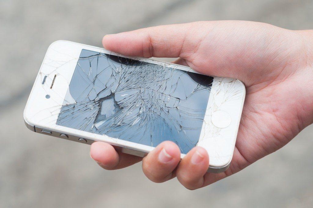 broken white phone on hand