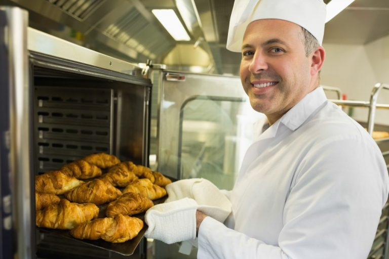 chef taking out the baked croissants from the oven