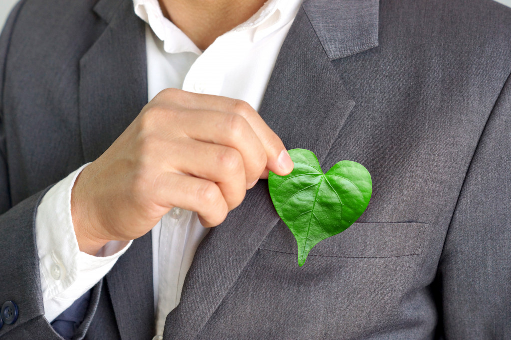 Businessman holding a heart-shaped leaf